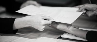 vrouw overhandigt een formulier aan man